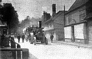 Old Photograph showing a traction engine accompanied by three smartly dressed gentlemen, followed by a horse and carriage which is full of gentlemen in top hats. The procession (approaching the photographer), is proceeding along Walsham's main street and is about to pass William Clamp's shop, now known as the Old Stores. The photograph appears to be of a funeral procession.