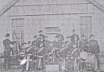 An old rather fuzzy black and white photograph showing a group of men, including Frank Nunn with a double bass, Wilfred Nunn and Harry Nunn, outside the Temperance Hall, all are wearing hats and they are holding various musical instruments.
