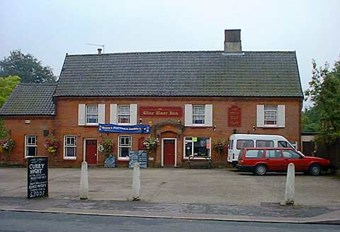"A photograph of the Blue Boar taken from the other side of the road. Large and long red bricked building with large flat straight tiled roof. A couple of vehicles in the car park and a Curry Night sign on the edge of the car park. A number of other signs and a banner are on the building itself as well as the pub's dark read sign saying ""Blue Boar Inn""."