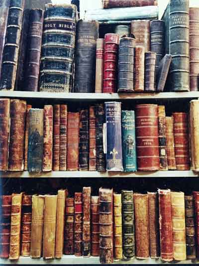 photograph of book shelves containing beautiful aged leather bound books with a range of very colourful, and some worn, spines