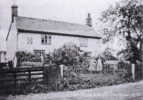 A black and white photograph of a the Crown and Anchor, Blo' Norton with gate, fence and shrubs in front of it and with a road alongside it.