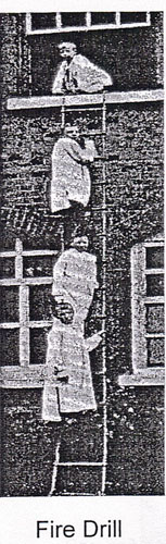 An old black and white photograph of four children on a ladder set against the brick wall of a building.
