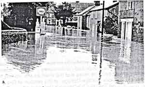 A copy of an old photograph showing a flooded street with a Shell petrol signs.