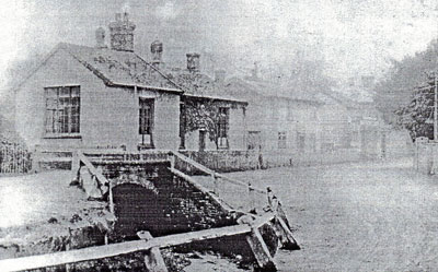 An old black and white photograph of a row of houses on The Street, including the Girls School, running from the left hand side of the photograph into the distance with the stream and bridge in front of the first house.