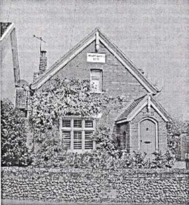 An old black and white photograph of a building showing the gable end with a porch towards the right with climbing plants around the window and against the porch.