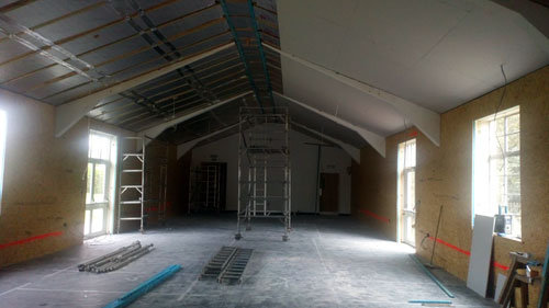 photograph showing the memorial hall works in progress, walls insulated and ceilings part insulated