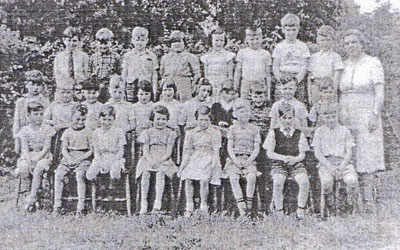 An old black and white photograph of three rows of children and one teacher Miss Sharman standing to their right.