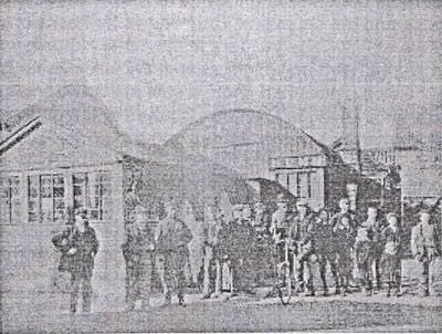 An old black and white photograph showing a line of men standing outside a couple of buildings known to be Nunn's Yard.