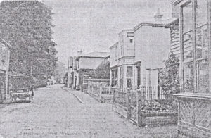 An old black and white photograph which is actually all very grey! It is looking down The Street in Walsham-le-Willows with buildings on the right, startign at Nunn's yard and trees on the left.