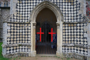 Two crucifixes faced with red poppies on the gate to the entrance porch, St. Marys church, Walsham-le-Willows.