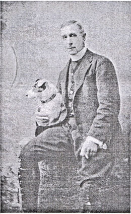 An old black and white photograph of the Rev. Arthur Briggs in a dog collar sitting facing the camera with a small dog on his lap.