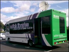 photograph of the green, black, white liveried suffolk mobile library van with satellite dish on roof