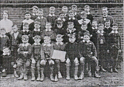 A black and white photograph of 3 rows of children with Mr Dove on the right and Miss Kerridge on the left.