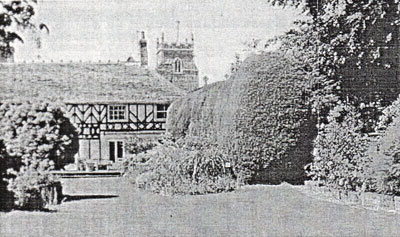 An old black and white photograph of a The Beeches, a timber framed house, with a church tower in the background and with trees and bushes in the foreground.