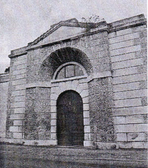 A black and white photograph of an entrance to a building showing a very solid door with a rounded top. There are no windows and this obviously the entrance to the prison.