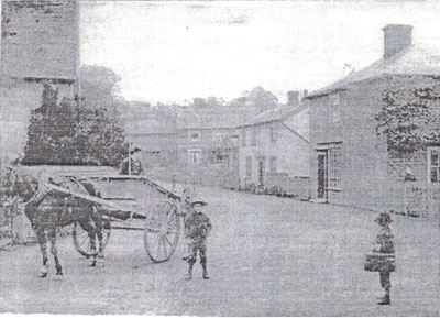 An old black and white photograph of a horse and cart and two children on The Street with the School House on the right.