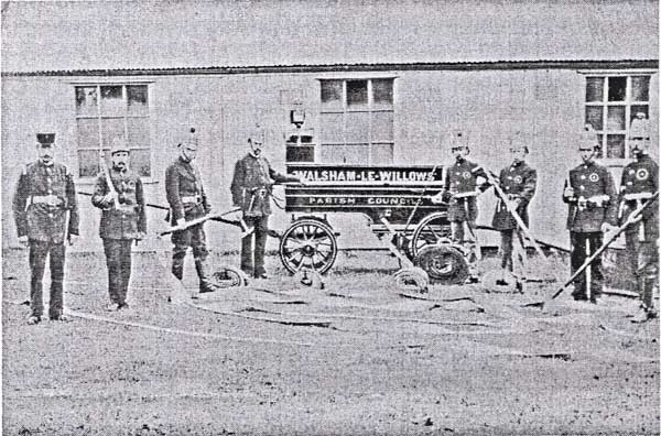 An old black and white photograph showing eight firemen standing around an old fire engine which was actually just a trailer which has the words Walsham-le-Willows Parish Council painted on it. In the background is an old wooden building known with three windows which was the 'Temperance Hall'.