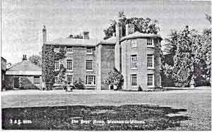 A black and white photograph of an imposing building with a large rounded bay window to 3 storeys and lawn in the foreground and trees behind the building.