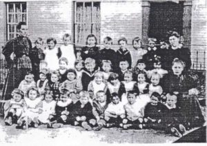 An old black and white photograph showing a group of schoolchildren in four rows and with a couple of teachers in the back row, all in front of a building.