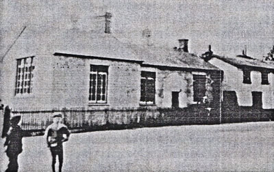 An old black and white photograph of Walsham School building with two boys in foreground on the left.