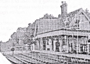 A black and white photograph of a railway station on the right with railway lines running from the front right away towards the left rear.
