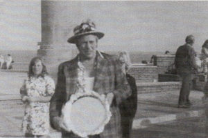 Charlie Studd on seafront at Lowestoft, proudly showiing his commemorative plate with onlooker and large pillar in background.