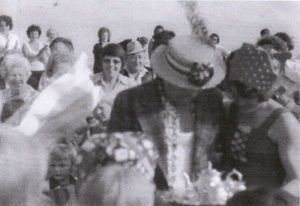 A black and white photograph of a man in a straw boater with his head bowed looking at something! Behind him are a lot of people looking on.