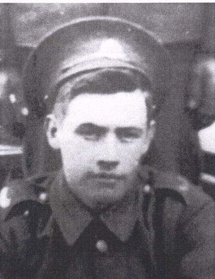 An old rather fuzzy black and white photograph of a soldier wearing a military cap on top of his head.