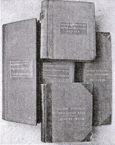 An old black and white photograph of a pile of old ledgers.