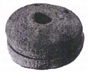 A black and white photograph of a round stone with a hole in the centre. This stone looks similar to the stones used by our Scottish friends when they participate in their sport of curling!