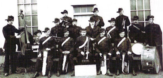 A black and white photograph of a group of men with their musical instruments.