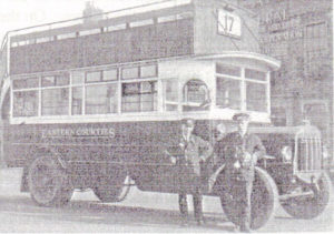 A black and white photograph of an old fashioned bus with the two men, known to be Fred Ellis and Neil Debenham, standing proudly by the front wheel.