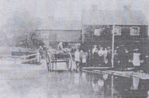 An old black and white old photograph of a flooded street with a cart and people.