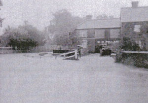 An old black and white old photograph of a very flooded street outside Rolfes the butchers shop.