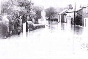 A black and white old photograph showing flood water in the middle of a street of houses.