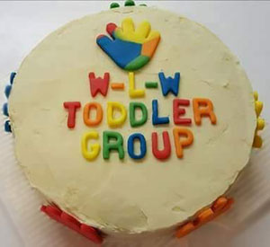 celebration iced cake decorated with colourful letters spelling out 'W-L-W Toddler group'