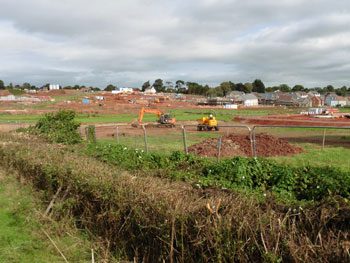 Photograph of digger in middle of green field commencing the layout of foundations for housing development